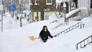 Schneechaos in Erie, Pennsylvania: Eine Frau schippt Schnee vor ihrem Hauseingang