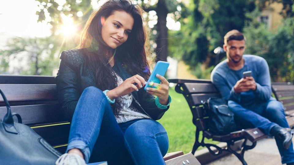 Ein Mann und eine Frau tippen auf ihren Handys