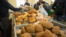 Eine Mitarbeiterin einer Tafel reicht einem Mann über Körbe mit Brötchen hinweg ein Brot