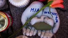 """Vor dem Drogeriemarkt in Kandel , in dem eine 15-Jährige erstochen wurde, stehen Kerzen und tönerne Hände mit """"Mia - warum?"""""""