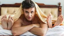 Verhütung: Mann im Bett mit zwei Frauen