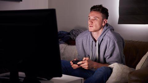 Mann sitzt vor Bildschirm und spielt