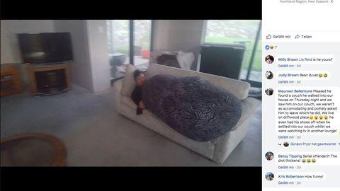 Ein Mann liegt unter einer Decke auf einer Couch und schläft