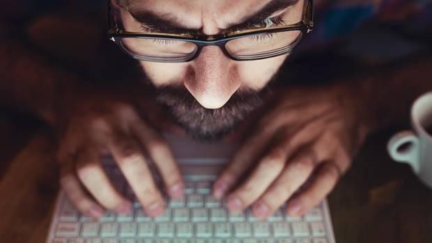 Ein Mann mit Bart gibt am Laptop sein Passwort ein und schaut dabei irritiert