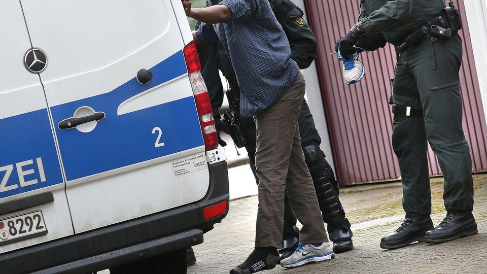 Polizisten untersuchen den Schuh eines Flüchtlings