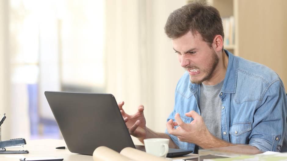 Ein Mann sitzt wütend vor seinem Laptop