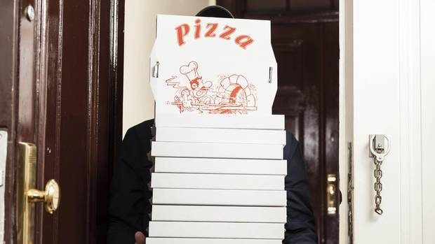 EIn Pizzabote trägt die bestellten Pizzen in eine Wohnung