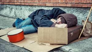 Obdachloser liegt auf Pappe