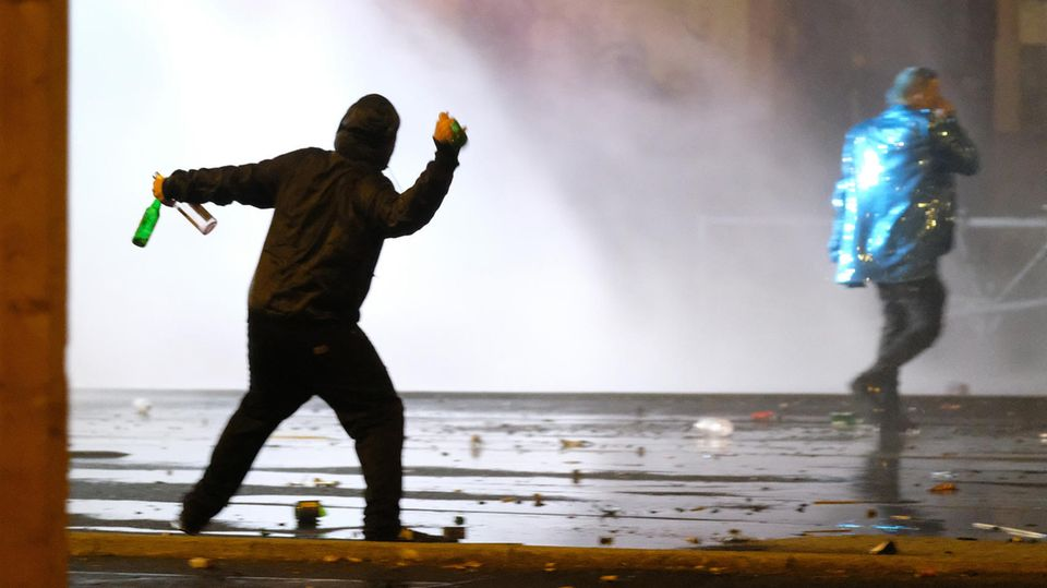 Ein Mann wirft bei Krawallen in Leipzig Flaschen Richtung Polizei - zu Gewalt-Studie