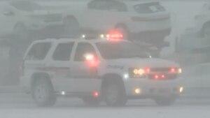 Im Schneetreiben fährt ein SUV der Polizei mit Blaulicht auf einer Autobahn. Auf der Gegenfahrbahn steht ein Autotransporter.