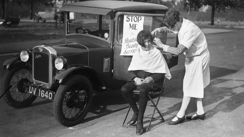 Ein altes Foto: Es zeigt eine Frau, die sich auf der Straße von einer Friseurin die Haare schneiden lässt