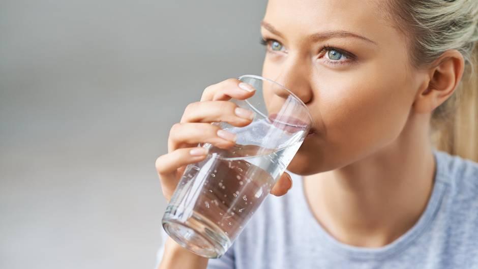 Eine junge Frau trinkt ein Glas Wasser
