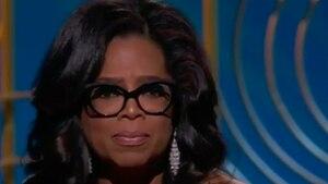 """Vor einer blauen Wand mit """"Golden Globe Awards""""-Logos hält Oprah Winfrey ihre Trophäe in die Kameras"""