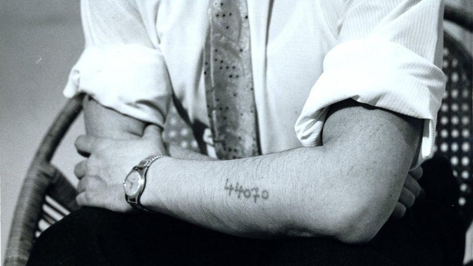 Ein Überlebender des Konzentrationslagers Auschwitz zeigt seine eintätowierte Nummer