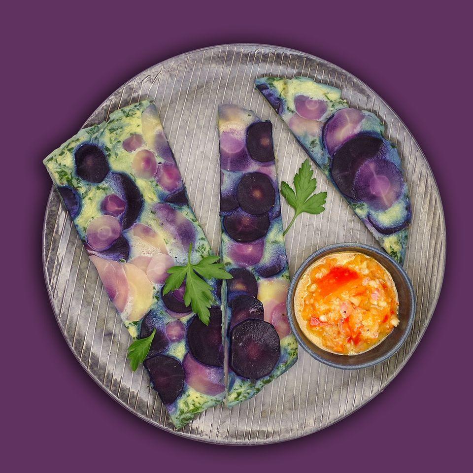Wurzel-Tortilla  Zutaten:  20 g Mandeln, 60 g Schalotten, halbiert, 200 g rote Paprika, entkernt, in Stücken, 40 g Weißweinessig, 80 g Olivenöl, 1025 g Wasser, 2 ¼ TL Salz, 4 Prisen Pfeffer, 1 Bio-Zitrone,, ½ TL Schale fein abgerieben, Saft ausgepresst, 130 g lila Möhren, in Scheiben (3 mm), 150 g Pastinaken, in Scheiben (3 mm), 50 g Zwiebeln, halbiert, 30 g Sahne, 5 Eier (Kl. M), 6 Stängel Petersilie, abgezupft, ¼ TL Paprikapulver rosenscharf, 2 Prisen Muskatnuss      Zubereitung:  1. Mandeln und Schalotten in den Mixtopf geben und 4 Sek./Stufe 5 zerkleinern.    2. Paprikastücke zugeben, 2 Sek./Stufe 5 zerkleinern und mit dem Spatel nach unten schieben.    3. Weißweinessig, 60 g Öl, 25 g Wasser, ¼ TL Salz, 2 Prisen Pfeffer und Zitronenschale zugeben, 20 Sek./Stufe 3 verrühren und in eine kleine Servierschüssel umfüllen. Mixtopf ausspülen.    4. 500 g Wasser in den Mixtopf geben, Varoma-Behälter aufsetzen, Möhren und Pastinaken einwiegen, mit ½ TL Salz würzen und 10 Min./Varoma/Stufe 1 garen. In dieser Zeit Varoma-Einlegeboden mit Backpapier auslegen, dabei darauf achten, dass die oberen seitlichen Schlitze frei bleiben.    5. Varoma absetzen, Gemüse gut abtropfen und ausdämpfen lassen.  Mixtopf leeren.    6. Zwiebeln in den Mixtopf geben, 5 Sek./Stufe 5 zerkleinern und mit dem Spatel nach unten schieben.    7. 20 g Öl zugeben und 3 Min./120 °C/ Stufe 1 (3 Min./Varoma/Stufe 1) dünsten.    8. Sahne, Eier, zerkleinerte Petersilie, bis auf ein paar Blätter, ½ TL Salz, 2 Prisen Pfeffer, Paprikapulver und Muskat zugeben und 15 Sek./Stufe 3 verrühren. Mischung auf den vorbereiteten Varoma-Einlegeboden geben, gedämpftes Gemüse darauf verteilen, in den Varoma-Behälter einsetzen und Varoma verschließen.    9. 500 g Wasser und 1 TL Salz in den Mixtopf geben, Varoma aufsetzen und 25 Min./Varoma/Stufe 1 garen. Tortilla mit Paprika-Vinaigrette und restlicher Petersilie bestreuen und servieren.