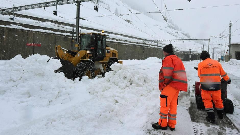Helfer befreien die Bahnstrecke nach Zermatt vom Schnee, unter anderem mit einem Bagger