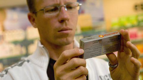 Ein Apotheker hält eine Packung Ibuprofen-Tabletten mit beiden Händen
