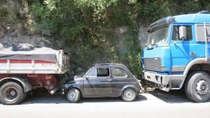 Ein Kleinwagen parkt eingequetscht zwischen zwei Lkw