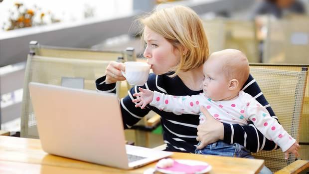 Eine Mutter mit Baby auf dem Schoß versucht, eine Tasse Kaffee zu trinken