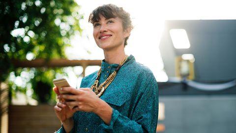 Lächelnde Frau mit Mobiltelefon