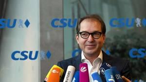 """CSU-Landesgruppenchef Alexander Dobrindt steht vor einer Glaswand mit lauter blauen """"CSU""""-Logos. Vor ihm ein Bündel Mikrofone"""