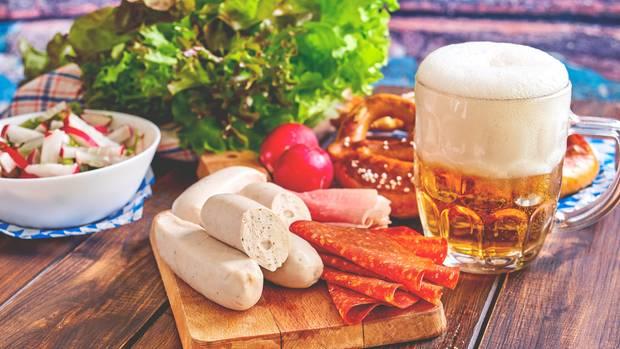Die wohl bekannteste Spezialität aus München: Weißwurst wird traditionell frühmorgens hergestellt und vormittags als Imbiss auf Märkten und in Wirtshäusern mit süßem Senf, Brezn und Weißbier gegessen. So isst man die Wurst übrigens richtig!