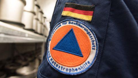Auf dem Ärmel einer dunkelblauen Uniform ist eine aufgenähte Deutschlandflagge und darunter das Logo des Bundesamtes zu sehen