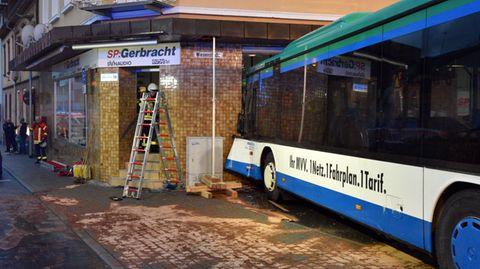 Einsatzkräfte von Feuerwehr, Polizei und Rettungsdiensten sichern in Eberbach die Unfallstelle, an der ein Schulbus am Morgen in eine Hauswand fuhr.