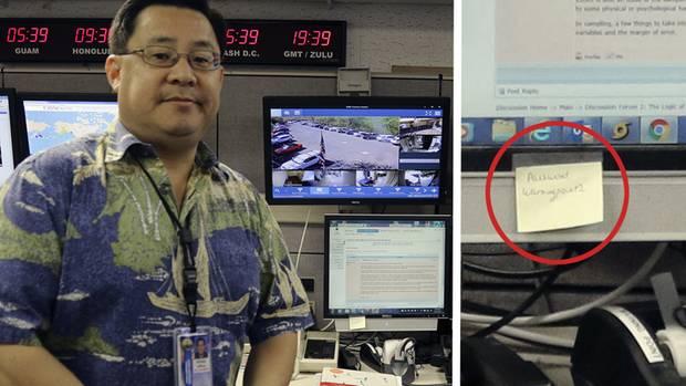 Ein asiatisch aussehender Mann mit Brille und Hawaii-Hemd steht vor einem Schreibtisch mit vier Monitoren