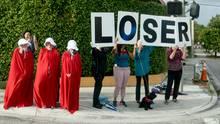 """West Palm Beach, USA, Präsident Donald Trump erfährt auf dem Weg zum Palm Beach International Airport, was diese Menschen von ihm halten: """"Loser"""" (""""Verlierer"""") steht auf den Schildern an der Straße, die Trumps Wagenkolonne nimmt."""