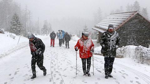 Wanderer gehen durch einen Schneesturm den Brocken im Harz hinauf
