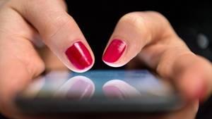 Zwei lackierte Fingernägel tippen auf einem Smartphone