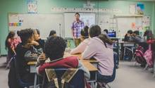 Kinder sitzen in der Schule im Unterricht und gucken nach vorne zum Lehrer.