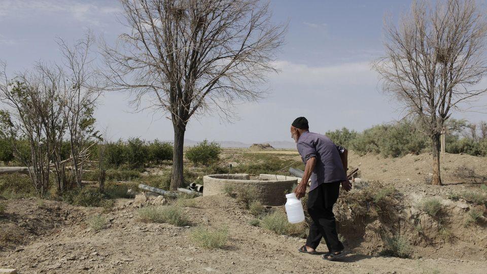 Ein Bauer an einem Brunnen in der Provinz Isfahan, das Wasser im Bohrloch ist brackig