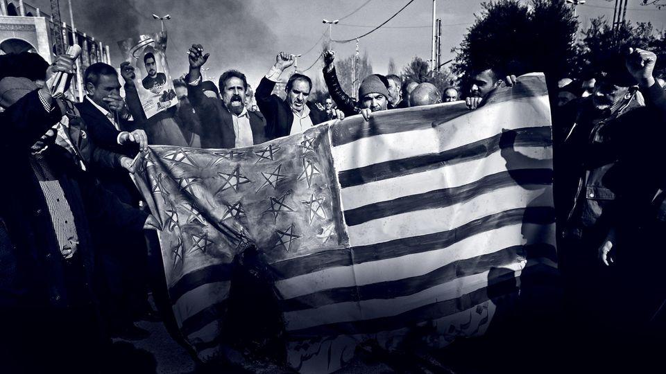 Regierungstreue Demonstranten verbrennen eine US-Flagge in den Straßen Teherans