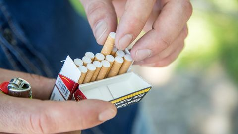 Ein Mann nimmt eine Zigarette aus einer Packung Zigaretten