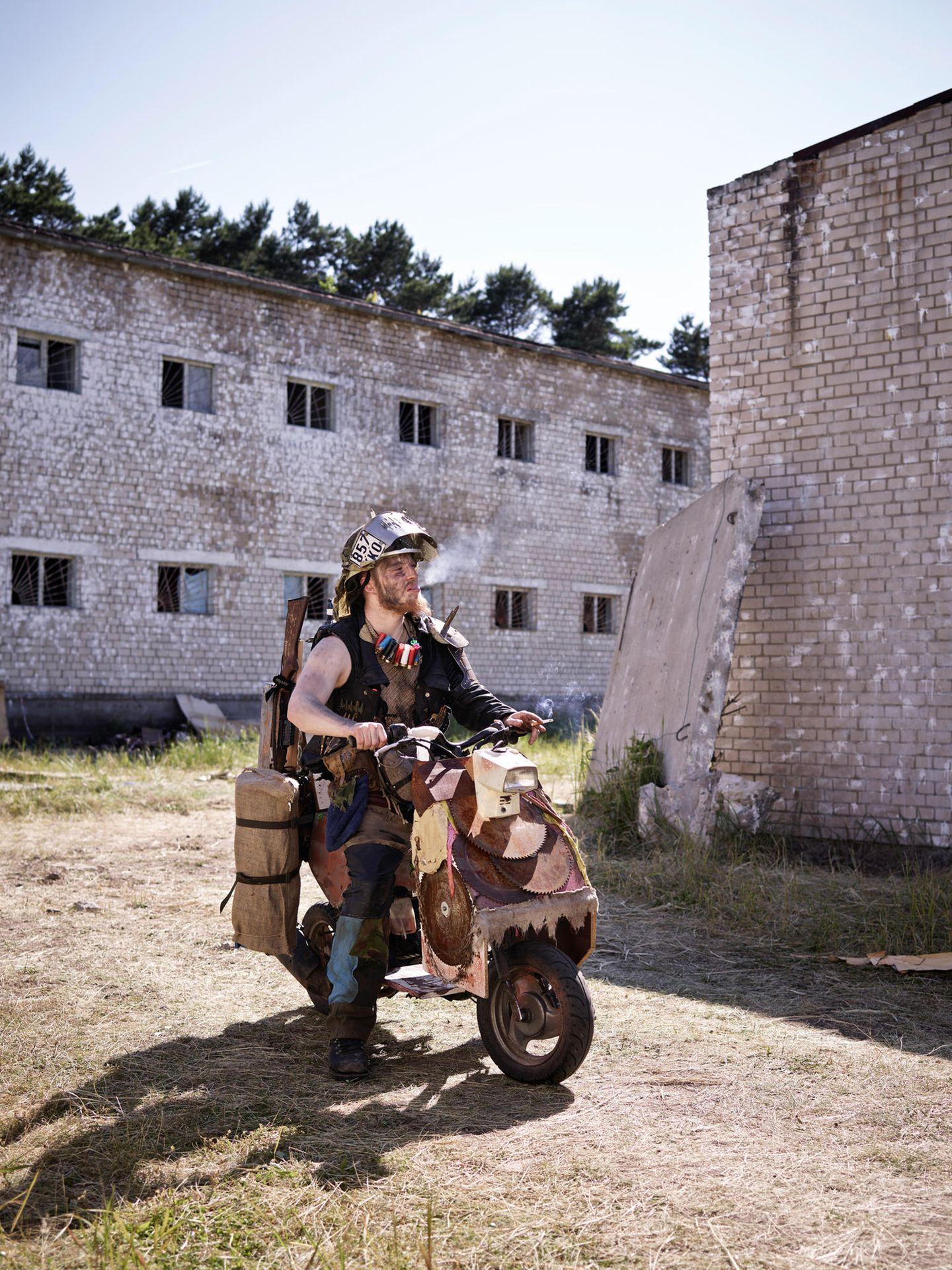 """Viel Rauch im Nichts: Bei """"F.A.T.E."""" spielen auf einem ausgemusterten Militärgelände in Sachsen-Anhalt bis zu tausend Männer und Frauen Weltuntergang. Dieses Zweirad hat überlebt und fährt Streife"""