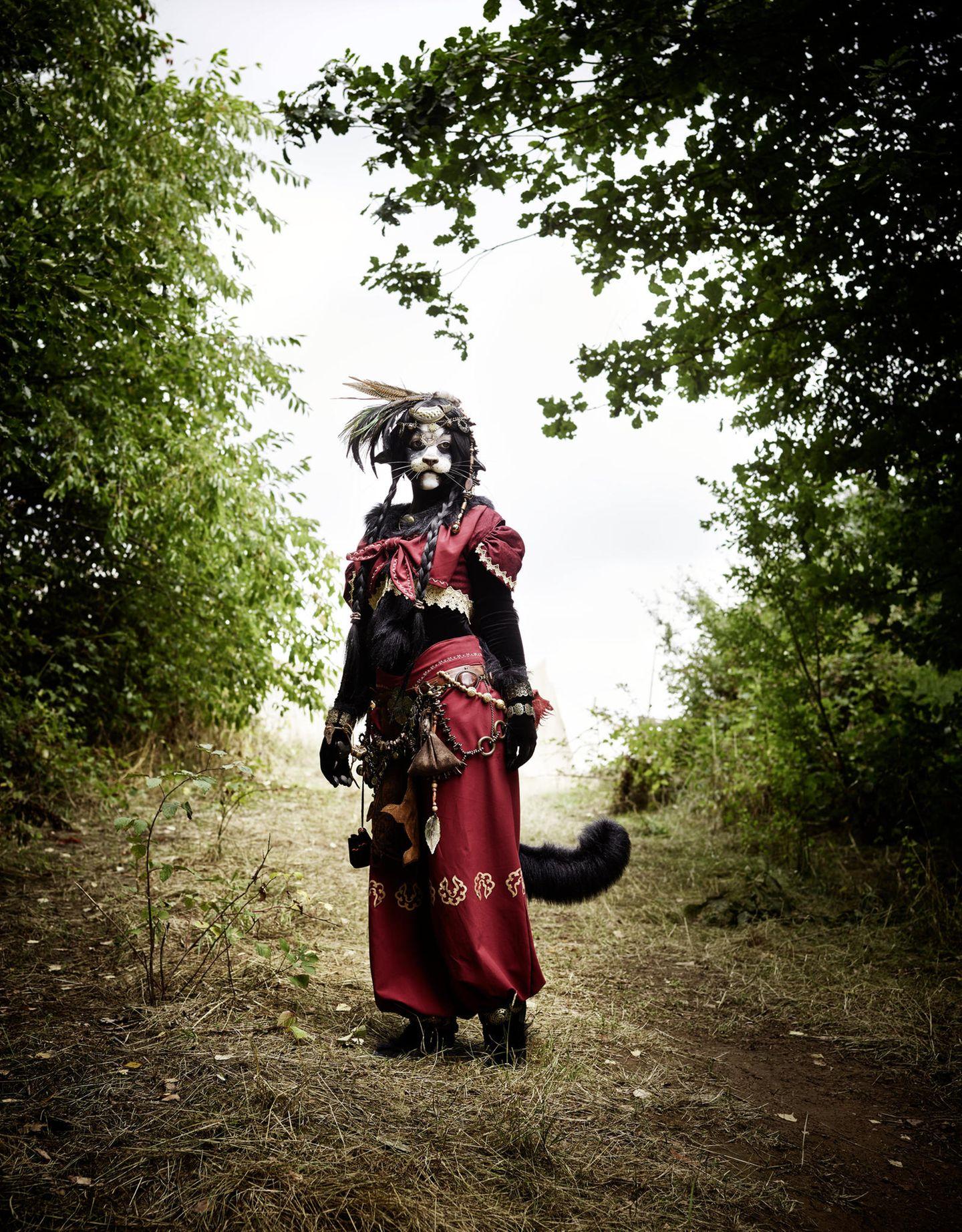 """""""Kimana"""" – Katzenwesen. 300 Stunden Arbeit stecken in dieser Aufmachung mit echten Falkenfedern. Und hinter der Maske steckt Mia aus München, die jahrelang an jedem Detail gearbeitet hat. Mia kratzt gern an der Oberfläche. Das echte Leben ist ihr ein bisschen langweilig"""