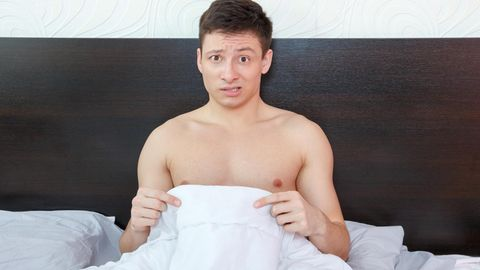 Ein sitzt halbnackt alleine im Bett und guckt etwas verwirrt, als er nach unten auf sein bestes Stück schaut