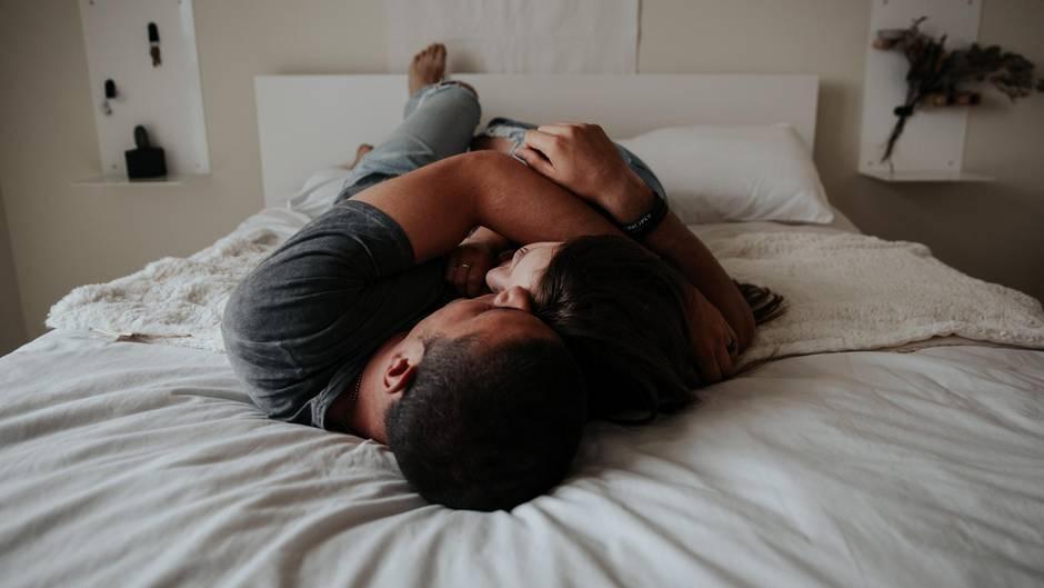 Mann und Frau liegen eng umschlungen auf dem Bett