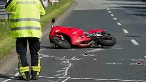 """Ein Polizist in neongelber Jacke mit """"Unfallforschung"""" auf dem Rücken steht vor einem kaputten Motorrad auf einer Straße"""