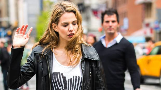 Frau geht weg, im Hintergrund der zurückgelassene Mann