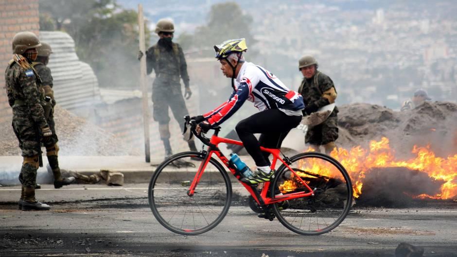 20. Januar: Jetzt aber schnell  Tegucigalpa, Honduras: Soldaten räumen brennende Reifen von der Straße, Oppositionelle haben sie angesteckt. Davon unbeeindruckt zieht dieser Radfahrer seine Runden. Am 27. Januar soll der neue Präsident Juan Orlando Hernandez ins Amt eingeführt werden.
