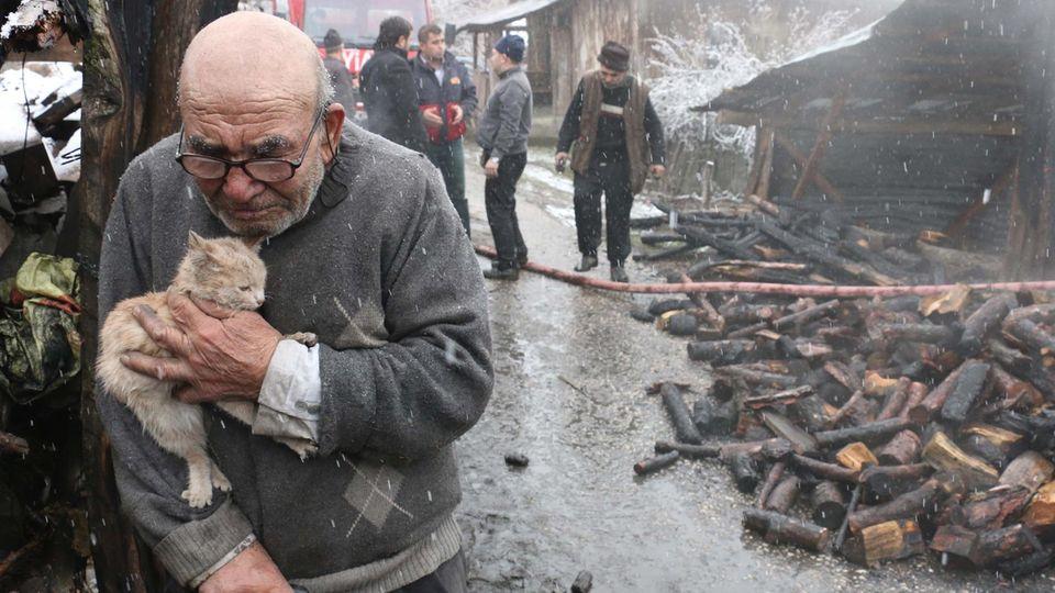 Ali Mese hält seine Katze auf dem Arm.