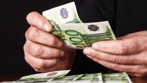 Hände mit 100-Euro-Geldscheinen, die gezählt und auf einem Tisch abgelegt werden.