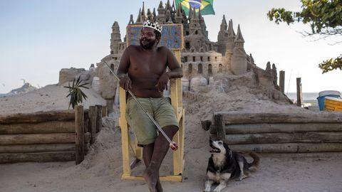 Der Brasilianer Marcio Mizael Matolias sitzt auf einem Holzstuhl vor seiner Strandburg in Rio.