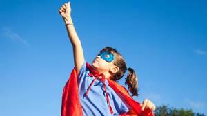 Ein Mädchen mit Superhelden-Verkleidung reckt die Faust hoch