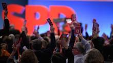 """Vor einer blau beleuchteten Wand und großem """"SPD"""" recken Delegierte auf dem Sonderparteitag ihre Abstimmungskarten hoch"""