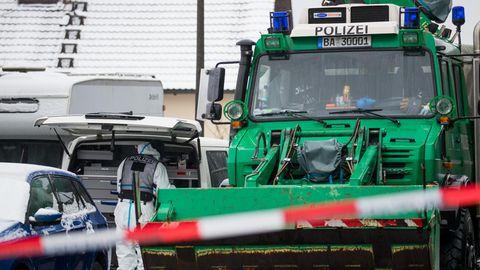 Vor dem Grundstück der Vermissten sucht ein Polizist in weißem Overall etwas in einem weißen VW-Bus, daneben ein grüner Unimog