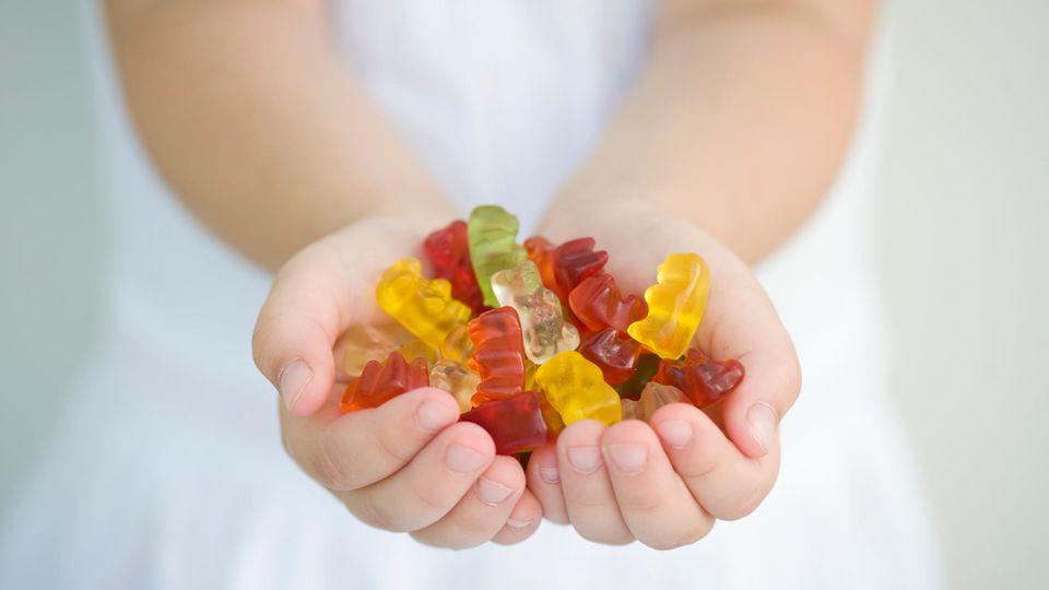 Mädchen hält Gummibärchen in den Händen